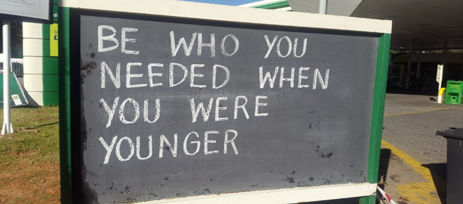 """Store sign that says """"Be Who You Needed When You Were Young"""""""